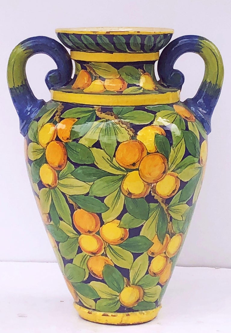 A fine large Italian majolica vase featuring a classic two handled body with a design of lemons and oranges and gold yellow and blue accents.