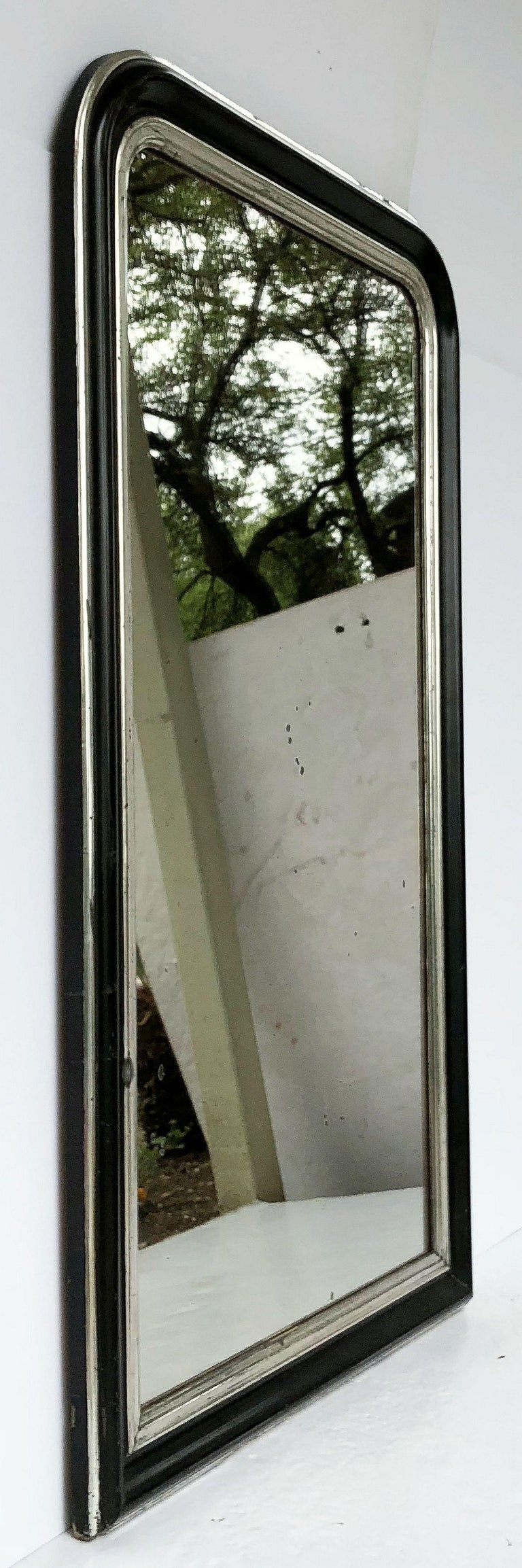 A handsome large Napoleon III period wall mirror featuring a lovely moulded surround and a design around the frame of black and silver leaf, with original mirrored glass.  Dimensions: H 53 1/2 x W 32 1/4