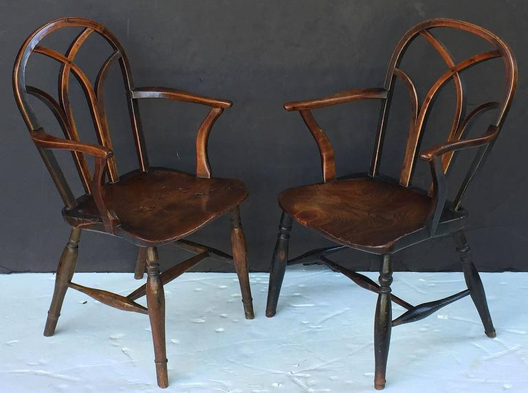 A finely patinated pair of English lowback Windsor armchairs of ash from the Georgian era, circa 1790, featuring interlaced bow backs with nicely turned arms, figured seats and handsomely turned legs. 