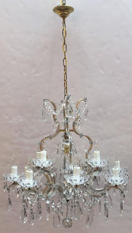 A lovely large Maria Theresa seventeen-light chandelier (or hanging fixture) of crystal, glass and gilt metal featuring serpentine arms, each candle light with dangling pendants and decorative bobeche.  Measures: 29 inches diameter  U.S.-wired and