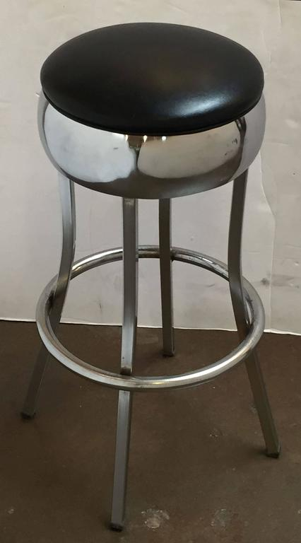 A set of six vintage bar stools of chrome steel, each stool with stationary seat of chrome with vinyl upholstery, resting on four leg stretcher support, each leg with rubber stop.  Priced individually - $1295 each bar stool.