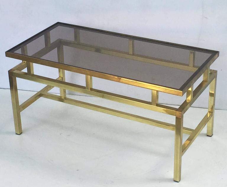A fine English rectangular coffee or cocktail table of framed brass with a smoked glass top.