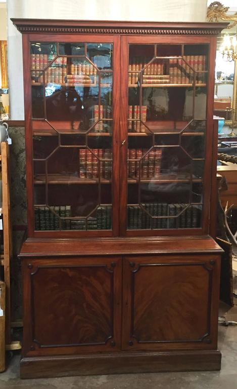 A fine large English bookcase of mahogany, featuring an upper tier with cornice and dentile moulding, two astragal glazed doors enclosing three adjustable bookshelves and the lower cabinet with two-paneled doors of flame-cut mahogany, fitted with