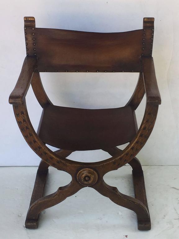 A comfortable Continental armchair (or lounge chair) in the X-shaped Roman style known as a Savonarola, featuring a finely patinated wooden body with aged leather back and sides and nail-head accents.