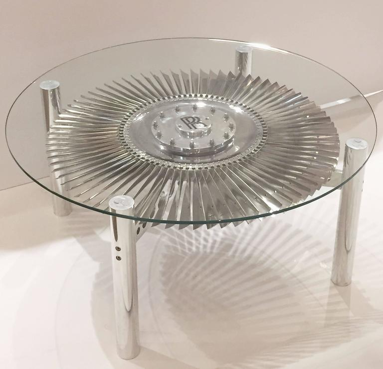 A stylish low cocktail or coffee table from England, featuring a round glass top (43 inches diameter) set upon a base with an authentic Rolls Royce rotating impeller from a British military jet engine, mounted to a four-post frame of tubular