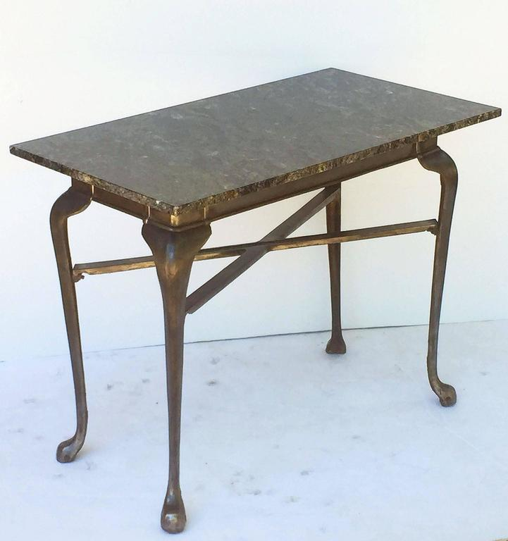 A fine English pub or bistro table of cast iron, made by Lawn and Howarth, Manchester, with a removable rectangular top of figured granite, set upon the iron base featuring a frieze with four cabriole legs and crossbar stretcher.