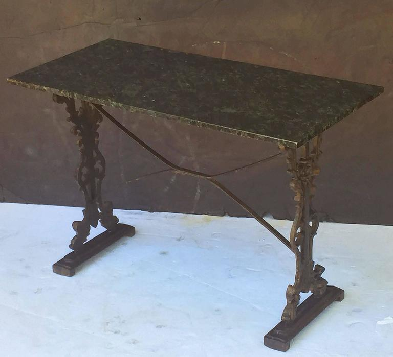 A pair of handsome English pub or bistro tables - each with a figured, rectangular granite top with a wood mount below, set upon a cast iron base with fine scroll work and sturdy bracket feet.  There are two available for sale. Individually priced -