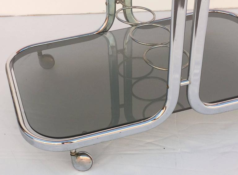 A handsome French vintage drinks cart table or bar trolley of polished chrome, with two smoked glass shelves, bottle holder rack on second shelf, and set upon rolling casters.