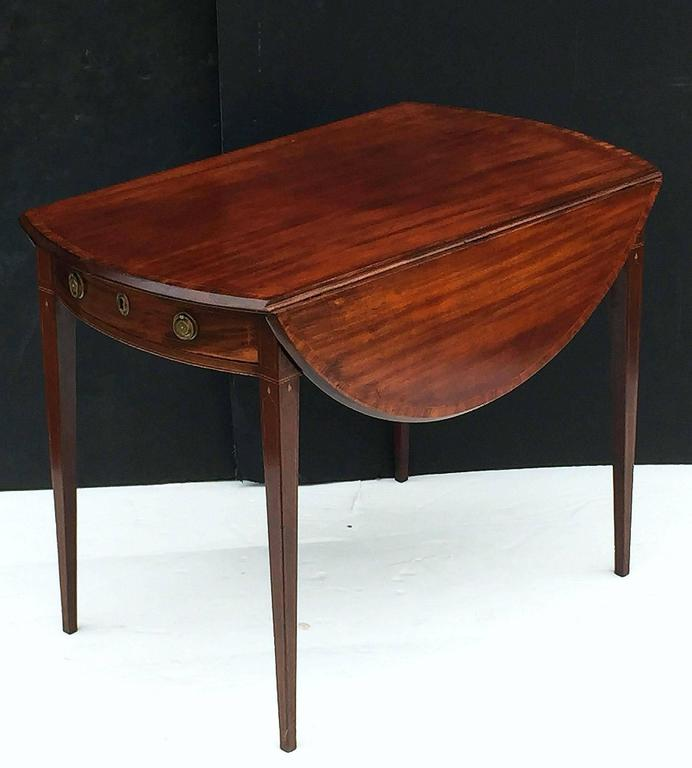 A fine English drop-leaf Pembroke table of mahogany in the manner of Sheraton, featuring a handsome oval top with crossbanding and fold-down sides, over a frieze with strung inlay, bowed drawer, and brass hardware, set upon four tapering legs with