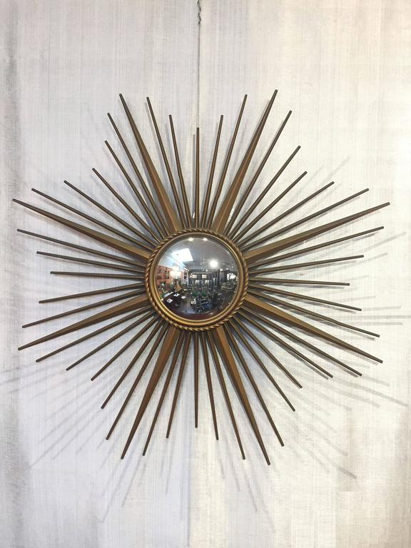 A fine French gilt metal sunburst (or starburst) mirror, 33.5 inches diameter, with convex mirrored glass center in moulded frame with rope motif trim by Chaty Vallauris.  With impressed mark of maker on back.  The Chaty Vallauris starburst or