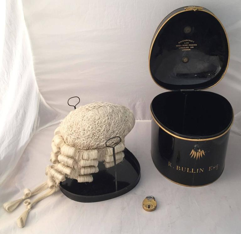 An English barrister's wig of woven horse hair in original tole box with lock and key, circa 1850-1890, featuring a barrister's wig with accompanying riser, in a fitted black tole box with gold accents and brass swan handle, the exterior marked