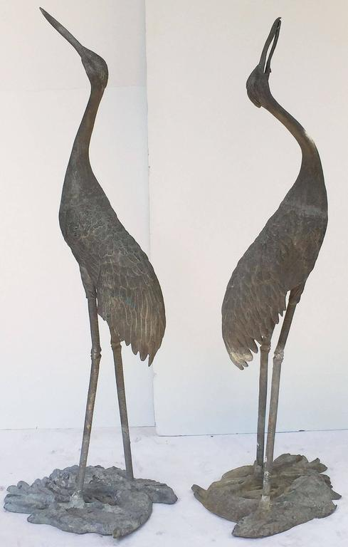 A pair of large ornamental lead herons or water birds from England, for display in a garden or water feature, each featuring a fine depiction of a heron bird standing on an oval base with a relief of fish.