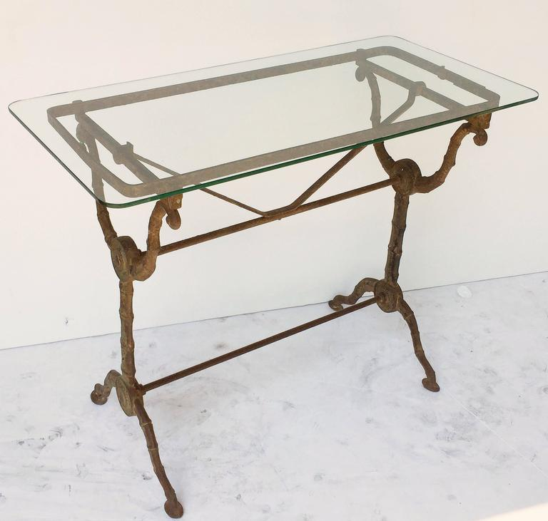 A pair of handsome English pub or bistro tables, each with a rectangular clear glass top, set upon a cast iron base with fine scroll work and sturdy segmented or faux bamboo supports.  There are two available for sale. Individually priced - $3495