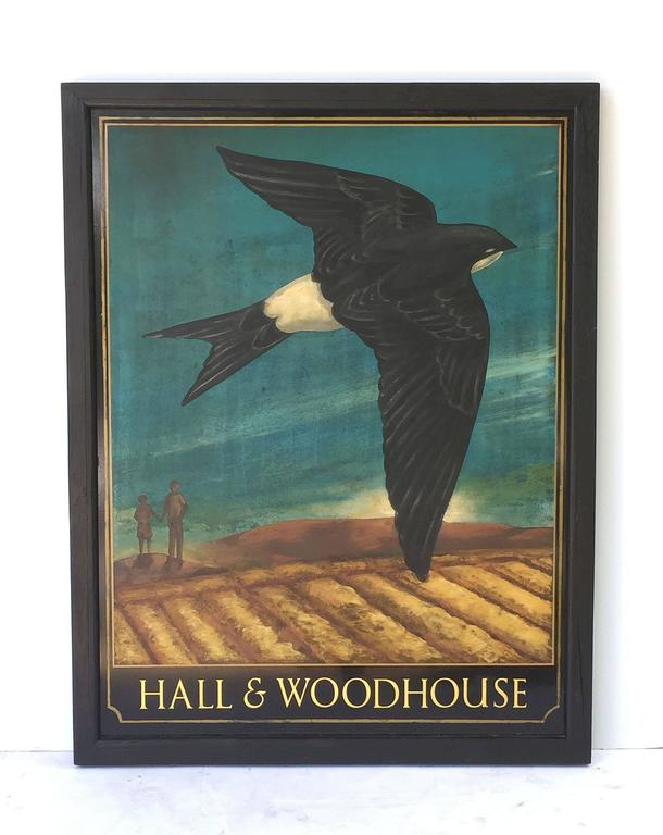 An authentic English pub sign (one-sided) featuring a painting of a swallow bird flying above a landscape with two figures in the background, entitled: Hall & Woodhouse  Hall and Woodhouse is a British regional brewery founded in 1777 by Charles