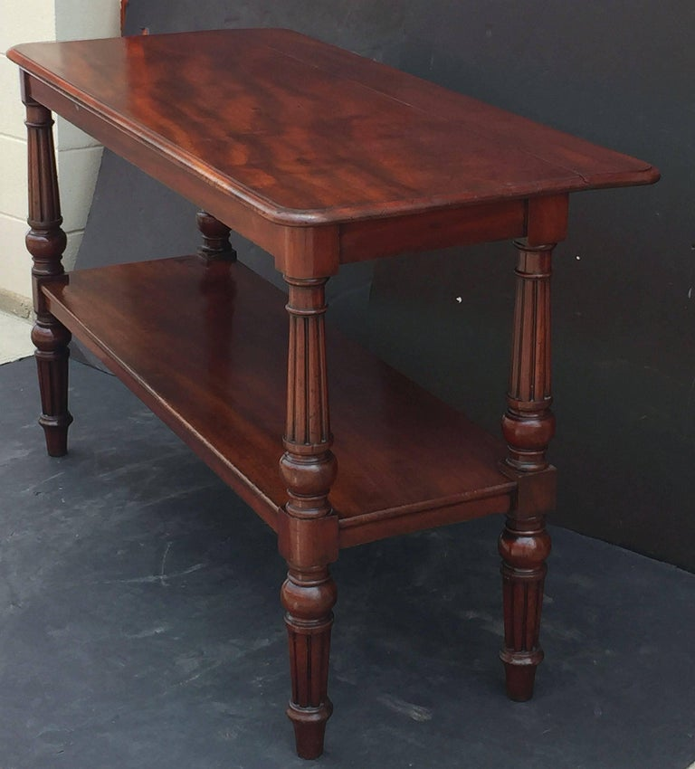 A fine English console server or buffet trolley table of flame mahogany from the William IV era, featuring a moulded rectangular top with extension or leaf to the back, allowing for extra depth. Set upon a frieze of four handsomely turned column