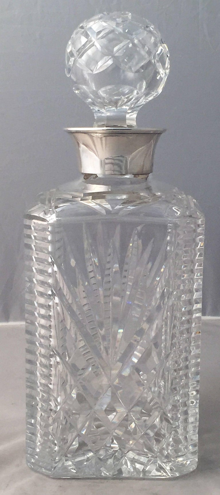 A handsome English four-sided spirits or whiskey decanter of faceted cut crystal with sterling silver collar and removable round stopper.