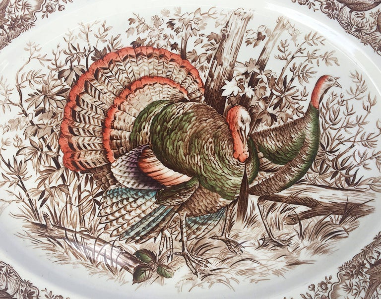A large vintage serving platter featuring the Wild Turkey, Native American brown and white transfer-ware pattern by the celebrated English pottery firm, Johnson Brothers.  With authentic midcentury brown label on reverse.  Perfect for the