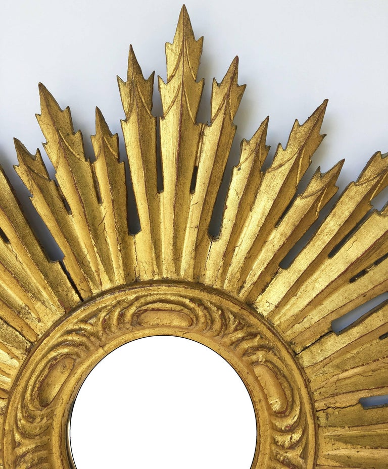 A lovely French gilt sunburst (or starburst) mirror, 24 inches diameter, with mirrored glass center in moulded frame.