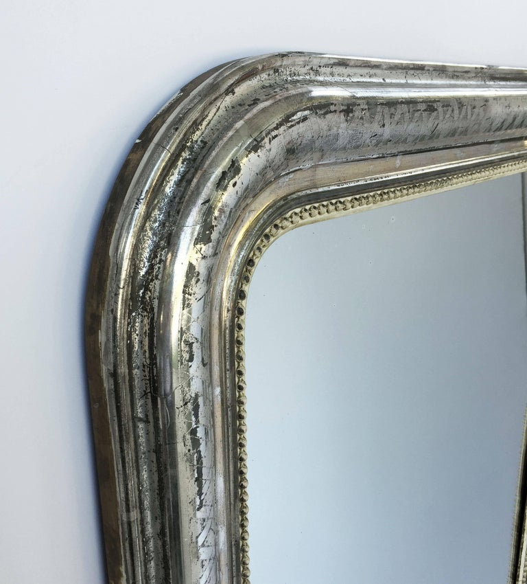 A fine Louis Philippe wall mirror from France, featuring a moulded surround with a beautiful patinated silver-leaf.  Dimensions: H 55 inches x W 34 inches  Other sizes available in this style.