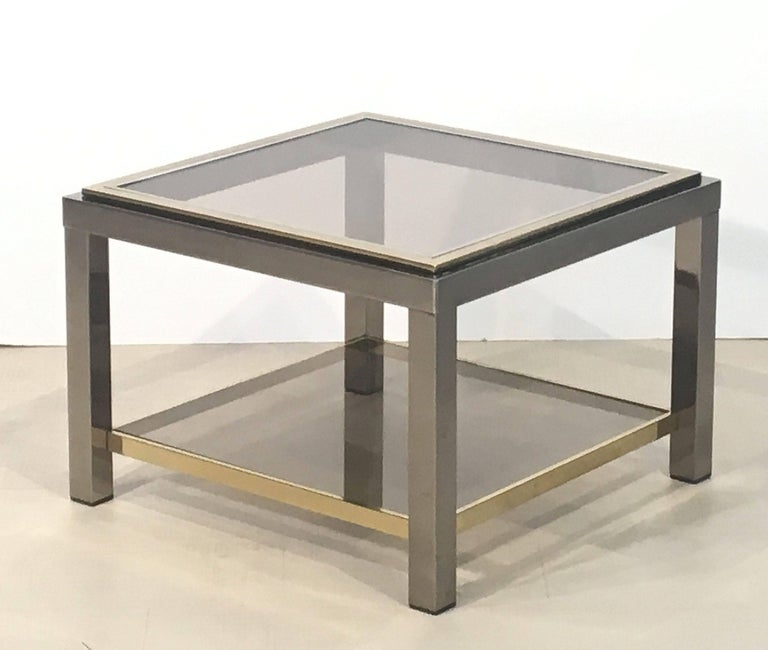 A handsome Italian square two-tiered low table or cocktail table of brass, chrome, and smoked glass by Zevi.  Zevi was a furniture manufacturer from Remanzacco, Udine, Italy.  The company is particularly known for their Modernist pieces for the home