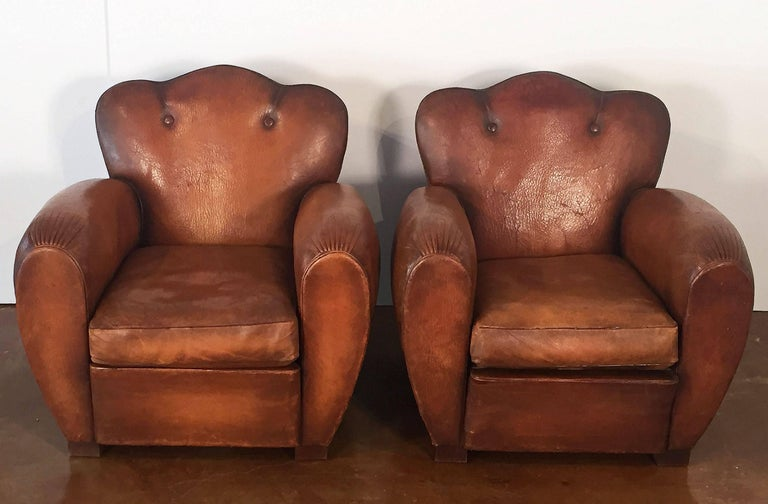 A handsome pair of French club chairs from the Fin d' Siecle to Art Deco eras, of upholstered leather with beaded trim to the front and sides, nail-head trim round the backs, and cushioned spring seats, featuring fine lines and deep seating comfort.