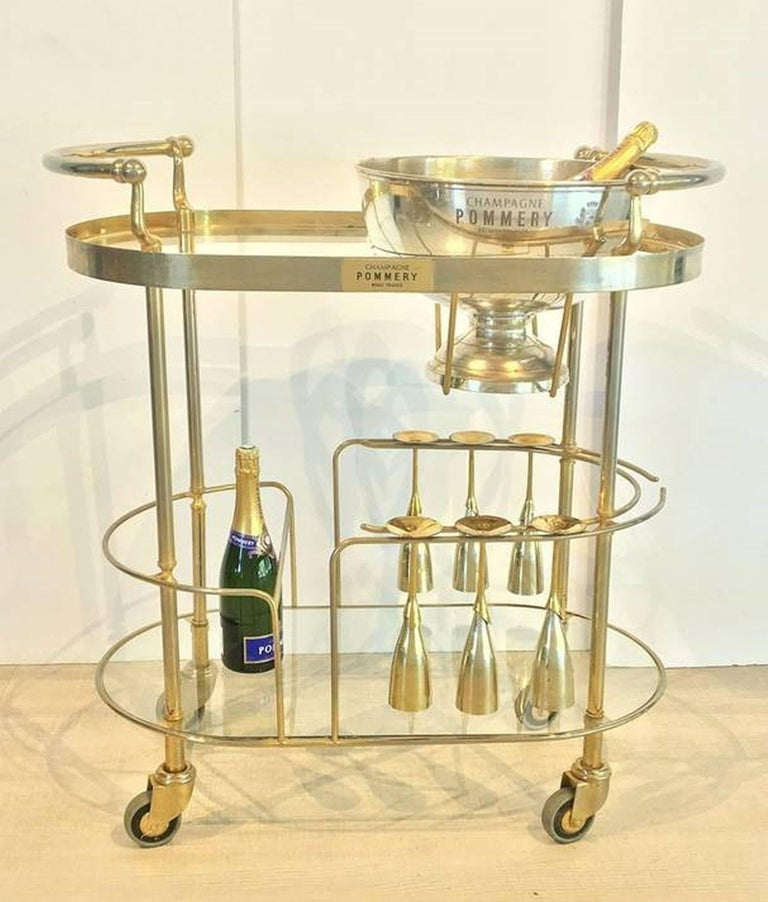 An Art Deco champagne trolley or rolling bar cart featuring a two-tiered curved frame of chromed brass and glass, the top tier with fitted silver bowl or wine cooler for ice, the second tier with six champagne flutes of silver and brass, on vintage