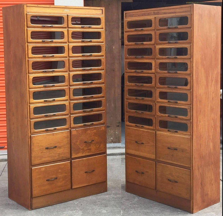 An exceptional pair of large haberdashery or haberdasher's cabinets from England featuring:  16 glass fronted drawers over four blind cupboard drawers .20 drawers total on each cabinet.  The fitted drawers with steel hardware.  Label at top