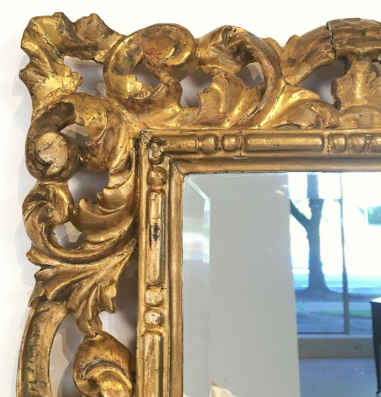 A fine Rococo rectangular beveled mirror with a carved giltwood frame.  Dimensions are H 22 1/2 inches x W 16 1/2 inches