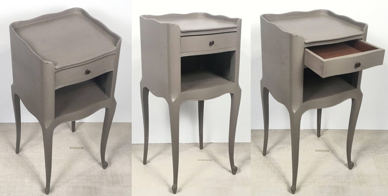 A pair of handsome French painted nightstands or petite cabinets (or bedside end tables), each featuring a moulded top over a frieze with three drawers, on a support with front-facing serpentine legs ending with hairy feet on a platform