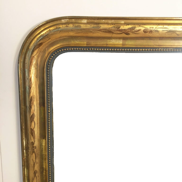 A handsome large Louis Philippe gilt wall mirror from France, featuring a lovely moulded surround and an etched foliate design showing through gold-leaf.  Dimensions: H 55 1/4 inches x W 39 3/4 inches  Other sizes available in this style.