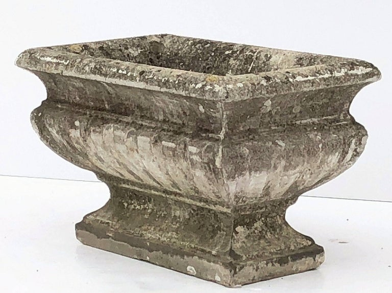 A fine large rectangular English pedestal trough or planter of composition stone, featuring a raised top on a shaped base.