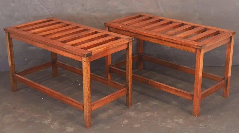 A fine pair of English luggage racks or rectangular low tables of mahogany, each feature a top of wooden slats over a support of four legs and stretcher. Can be used as stools as well.