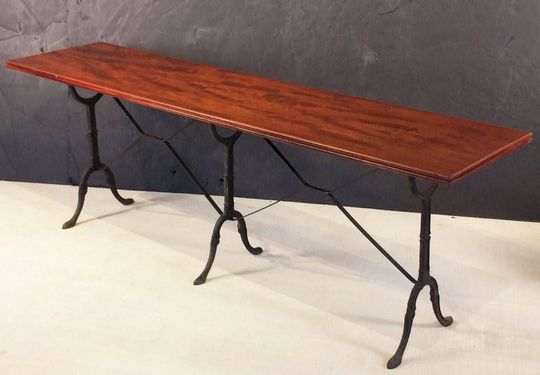 A fine English pub or bistro console table, featuring a moulded rectangular wooden top, set upon a cast iron base with fine scroll work and sturdy feet.