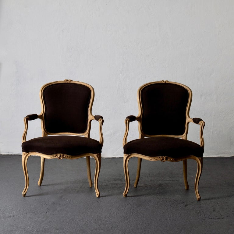 Armchair pair Swedish Rococo yellow brown Sweden. A pair of armchairs made during the Rococo period in Sweden 1750-1775. Frame is painted in a hay yellow. Details carved in roses and s shapes. Upholstered back, and armrests in a brushed cotton
