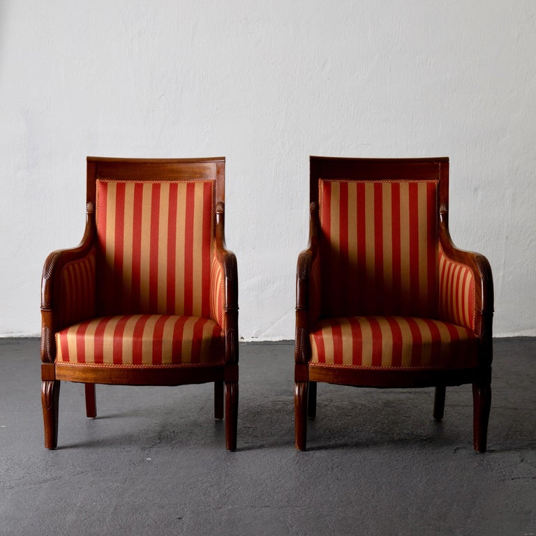 Chairs pair of Empire French mahogany, France. A pair of chairs / bergeres made during the Empire period (1810-1830) in Sweden. Frame from a lighter mahogany with leaf-shaped decor. Upholstered back, seat and armrests.
