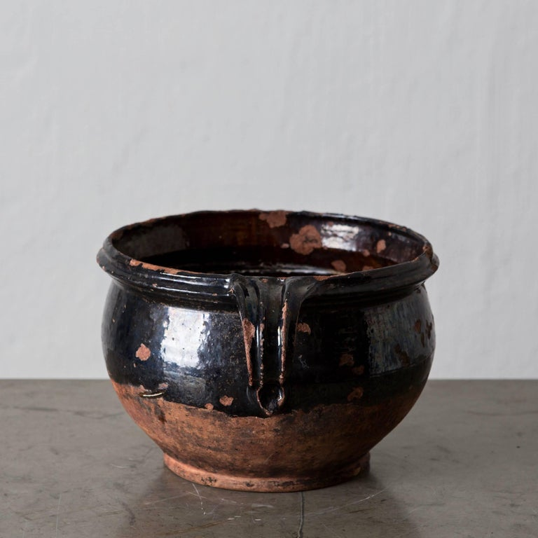 A terracotta jar pot with black salt glaze made in southern Sweden during the 19th century.