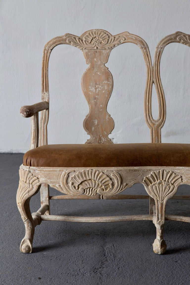 A Swedish sofa/bench made during the Rococo period Original Light paint Sweden, 1750-1775. Frame with beautiful carvings such as the Rocaille shape and feet ending in a claw and ball. Seat upholstered in a medium brown leather with a vintage feel.