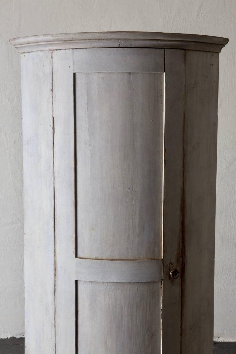 A corner cabinet made during the Gustavian period and early 19th century in Sweden. White distressed finish with a dark gray inside. Both finishes have been restored. Legs have also been restored.