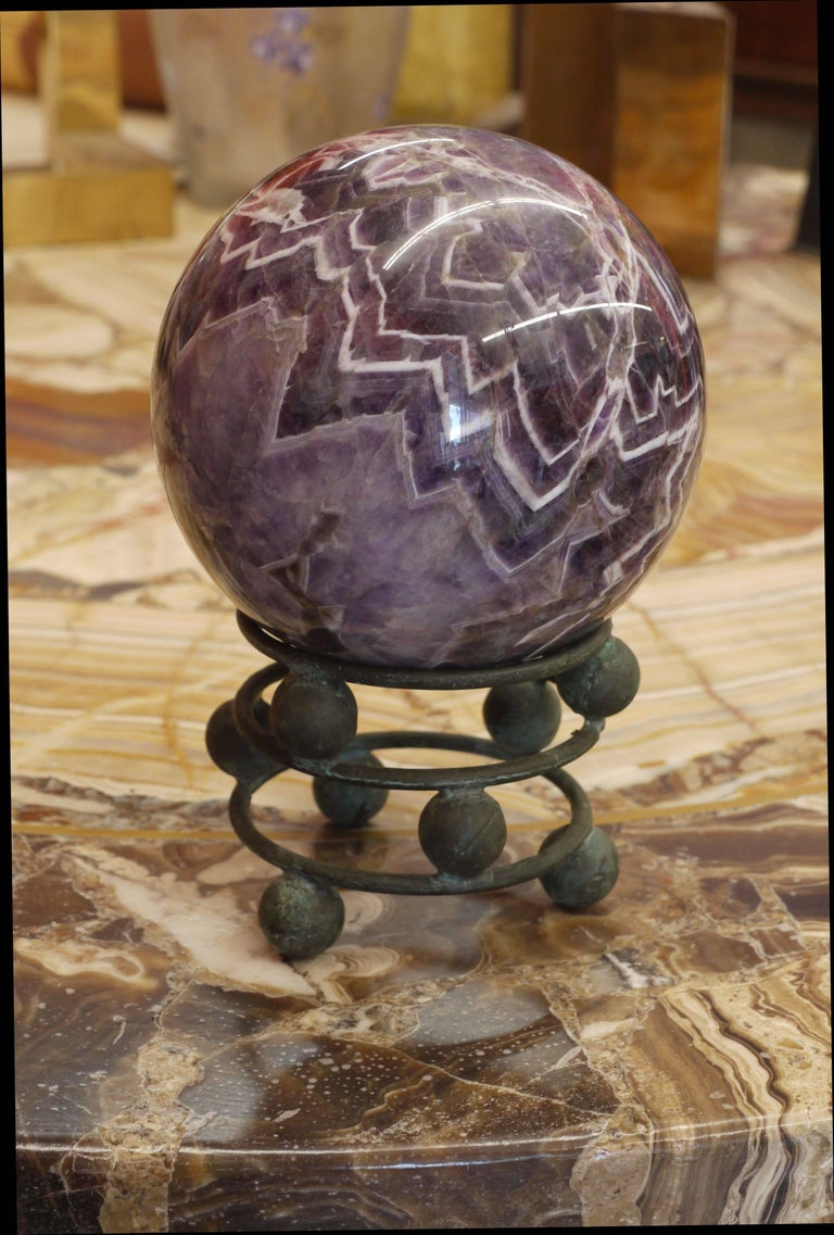 Large 5.5 inch polished amethyst sphere with incredible pattern sitting on top of a vintgae bronze stand made of spheres and rings. The stand almost looks like the whole thing is balancing. Amazing construction of the stand as it seems as it's all