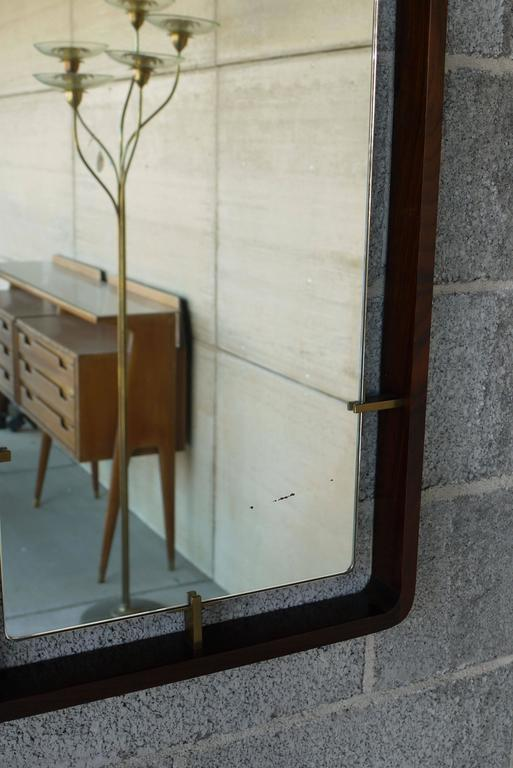 Handsome Italian mirror with polished edges suspended by brass hardware floating inside of a rosewood frame. The rosewood frame is finger jointed together on the corners and the construction overall is incredibly high end.