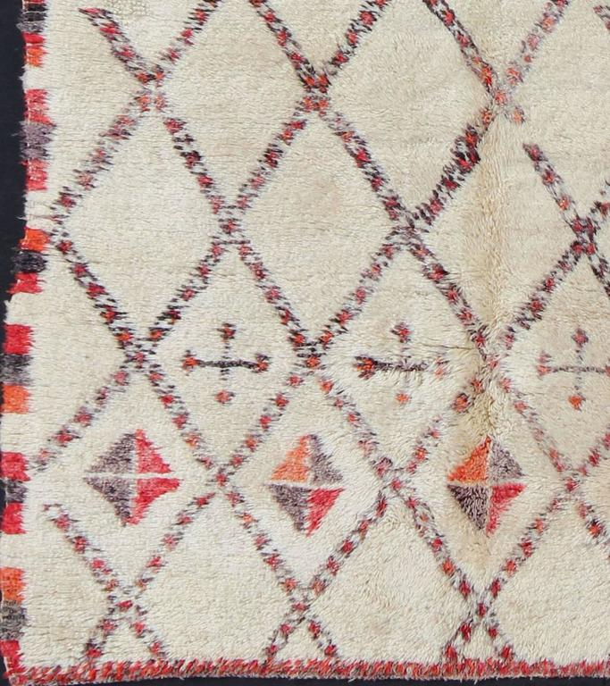 Woven in light, creamy, hand-spun wool with muted red, gray and light charcoal symbols, this gorgeous Moroccan rug has a sophisticated lozenge-based grid design that encompasses the entirety of the carpet. The eight-pointed star and cypress tree