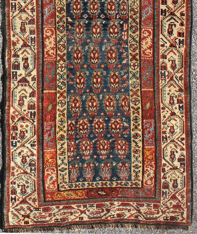 This antique runner was woven in far northwest Persia in the area bordering the Caucasus. The vibrant color and saturation of its finely drawn elements are enhanced by their placement against a deep indigo field. The main border is composed of