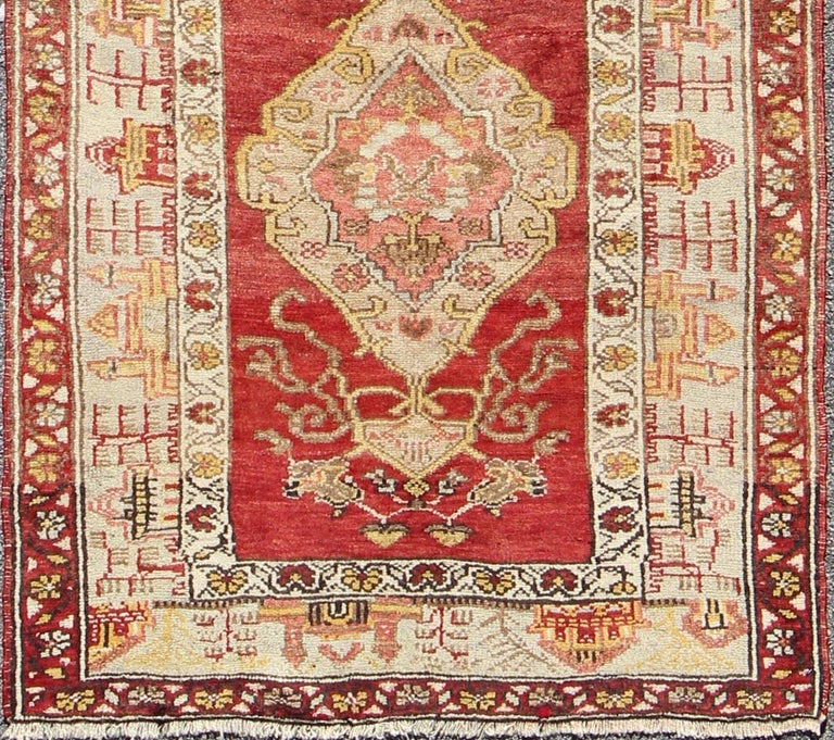 This colorful Oushak carpet rests beautifully upon a field of elegant red. A large medallion of brown, taupe, yellow and gray takes center stage and is well balanced by four prominent organic corner motifs composed of various muted taupes and light