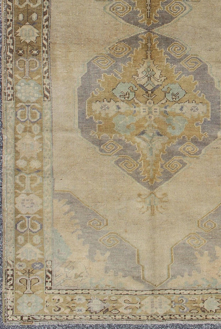 This vintage Oushak beautifully illustrates the impressive craftsmanship and design of Turkish weavers. This muted design gives the illusion of large muted medallion flowing through the rugs centre field of greyish, taupe hues. Linear branches on