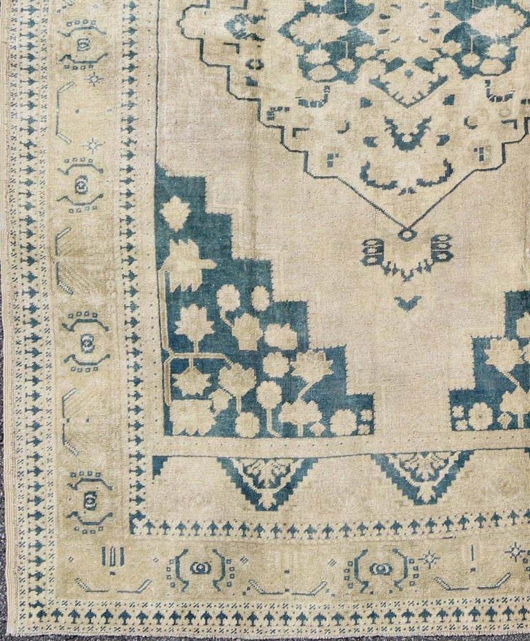 This geometric Turkish Oushak carpet rests beautifully upon an ivory background with a cream border. A blue outlined medallion takes center stage and is well balanced by four organic corner motifs composed of the same blue and neutral colors.