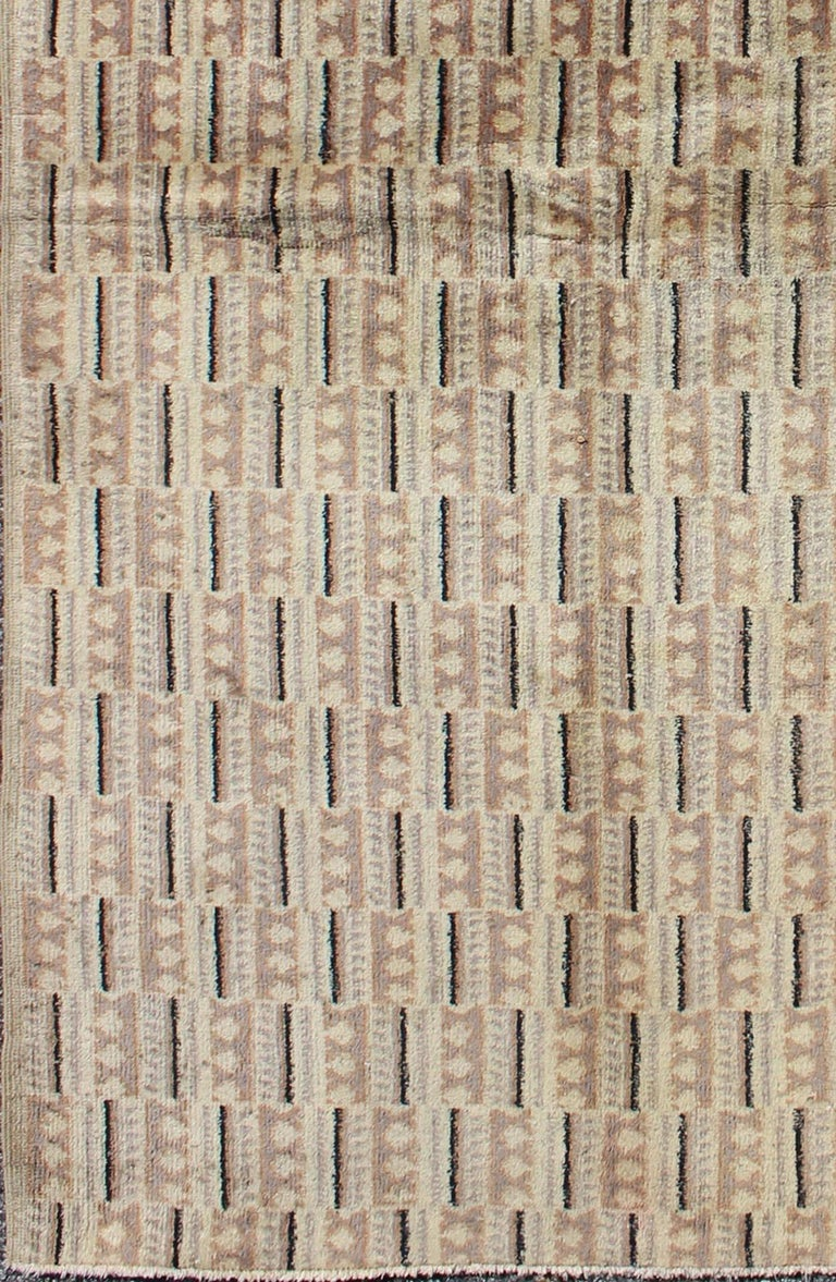 This finely handwoven Zeki Müren vintage rug displays a unique design and color combination. Colors include taupe, brown, raffia and ivory. Measures: 3'7 x 6'6.