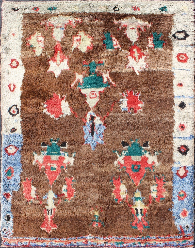 This antique Tulu rug showcases a free-spirited design with stunning colors of blue, brown, green, red and cream. The high pile of this rare rug is angora wool, which adds sheen to this eclectic piece. Measures: 4'1 x 5'5.