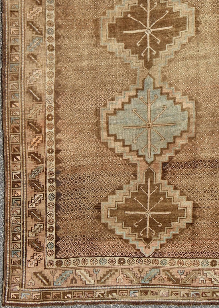 Set on a camel and brown background and accented by neutral cream and light blue, this tribal Turkish Oushak rug showcases five geometric medallions that stretch throughout the entire field of the rug. A multi-tiered border with repeating geometric