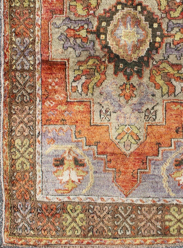 Vintage Colorful Turkish Oushak Rug in Orange, Purple, Green and Brown. This piece a compelling and beautifully woven Oushak carpet that was made in Turkey during the middle of the 20th century. This vintage carpet beautifully communicates an