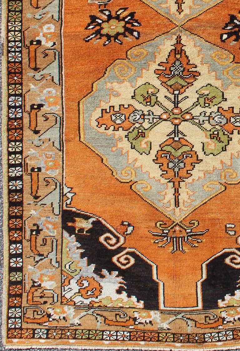 Vintage Turkish Oushak with Orange, Light Blue, Gray, Light Green and Brown This beautifully colored Turkish Oushak features two medallions and a highly detailed design set on an orange background with dark brown and light taupe colors and stunning